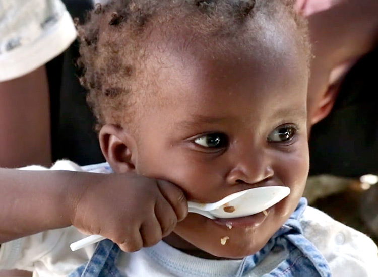 Haitian child eating manna pack food.
