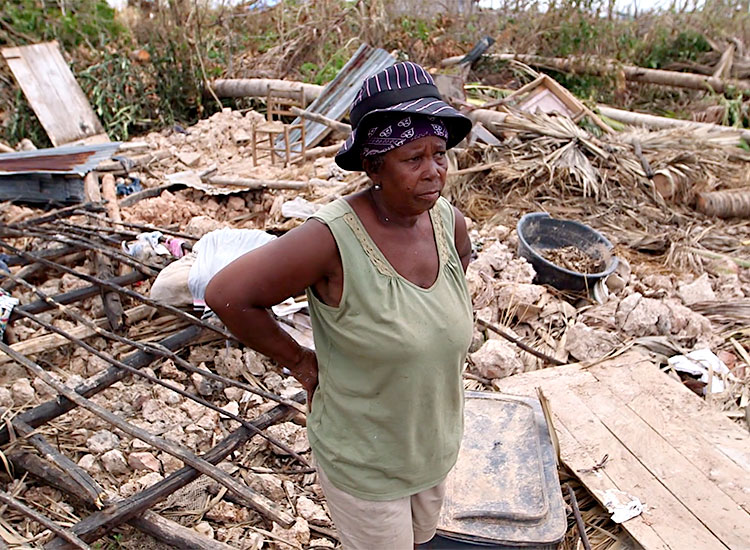 Haitian women stands inside her flattened house.