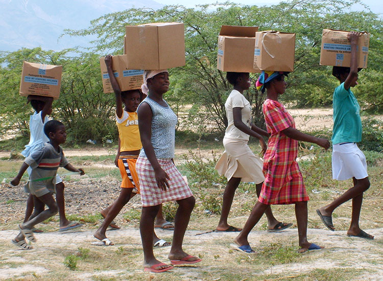 Haitian women carry their food boxes back to their homes.