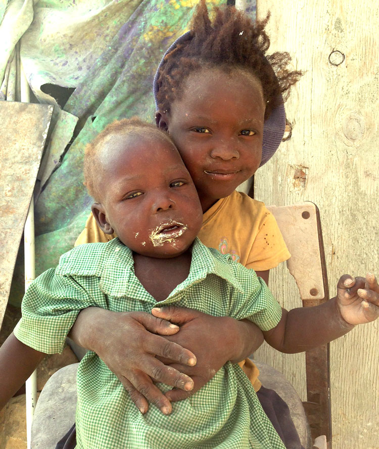 Hungry children eat a handful of mud to keep their hunger pains away.