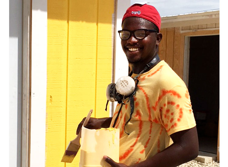 Stanely is painting the new school for Miracle Village.