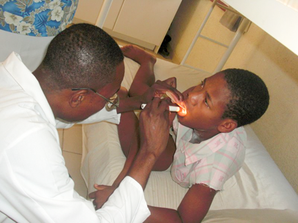 Dr Mardy examines a boy at our medical facility in Haiti