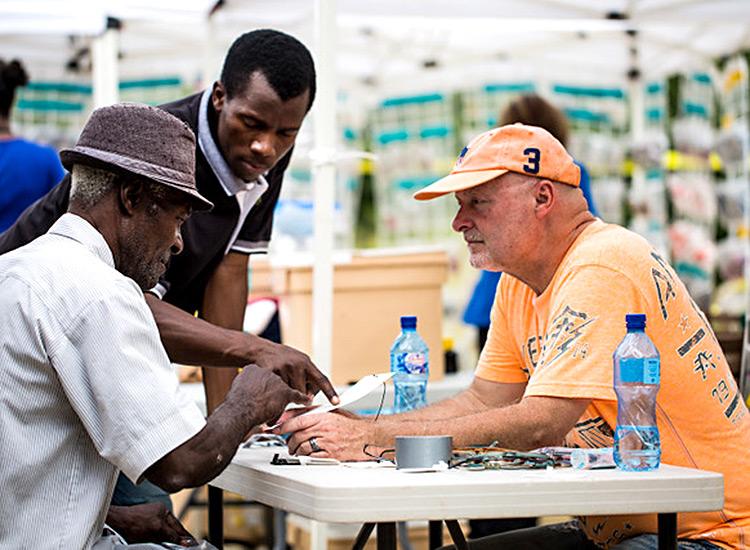 David George assisting elderly Haitin with new glasses