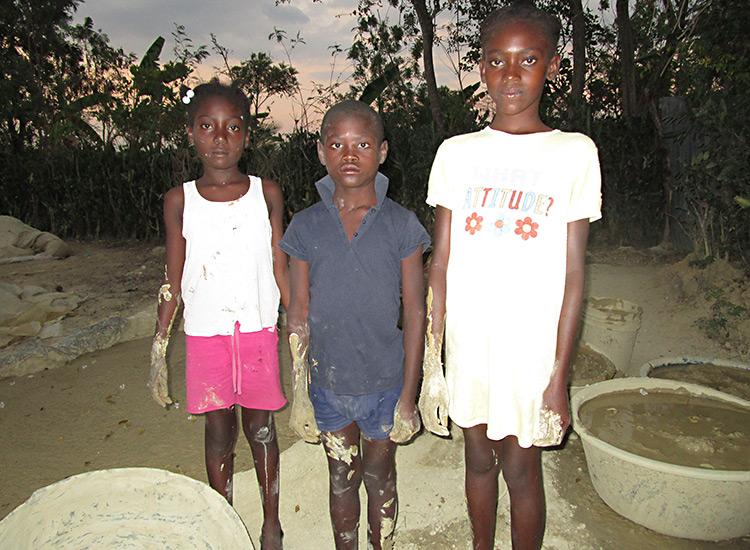Haitian children working making mud cookies