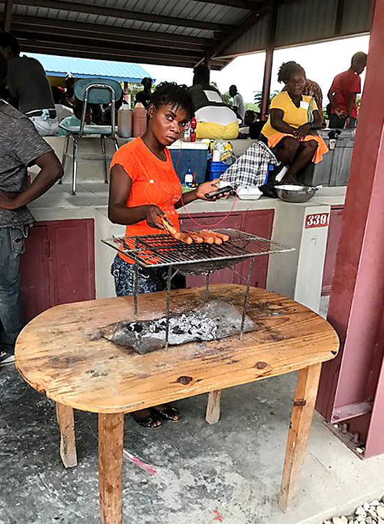 Haitian woman cooking hot dogs at the marketplace.
