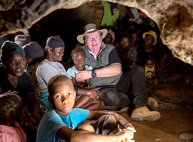Bobby sits with poor Haitian familes inside a cave