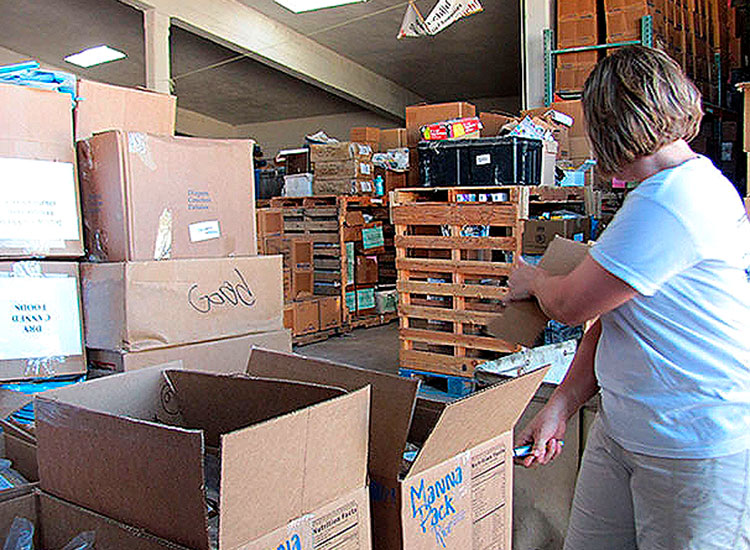 Volunteers assemble food packs at several of the company's packing locations.