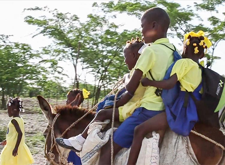 Young children travel by donkey to reach their temporary school.