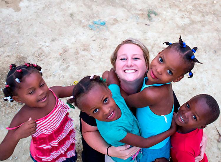 Children greet Kaeli with hugs of joy.