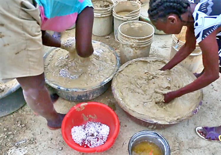 Women in Sabaterre make mud cookies.