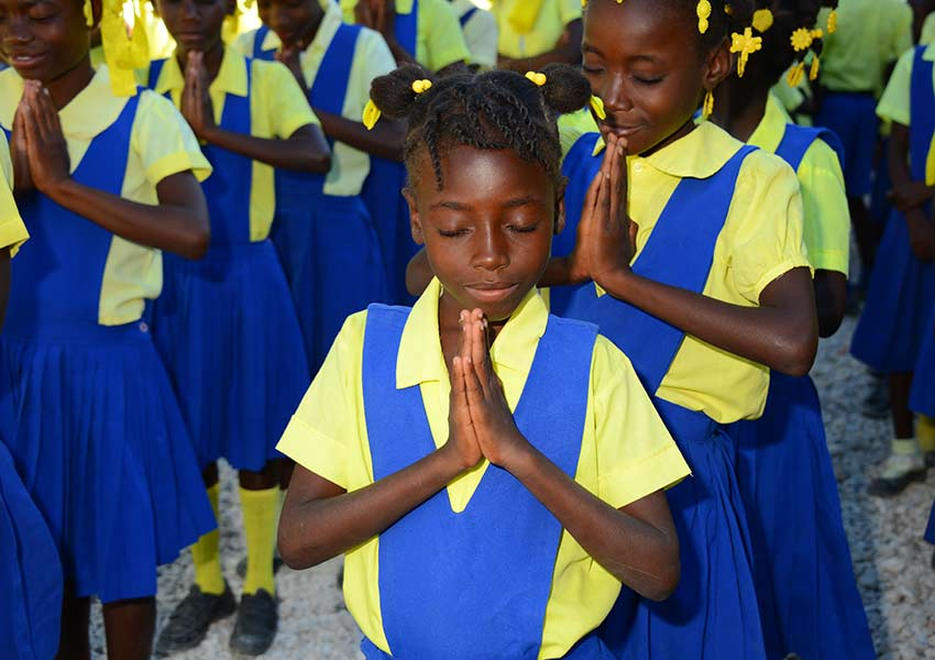 Students pray before the start of school each morning.