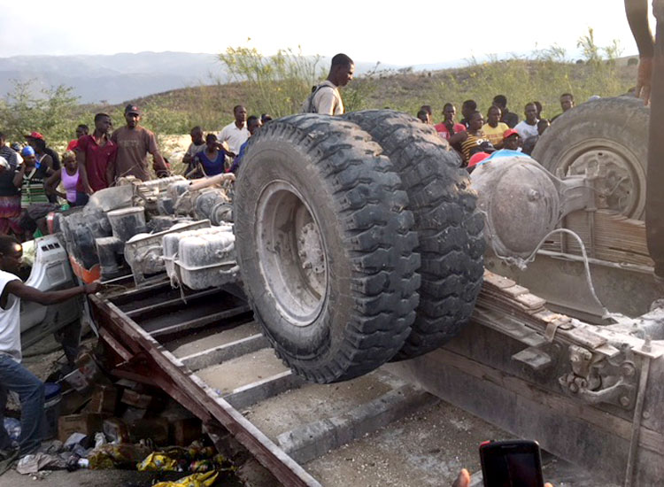 A horrible accident involving a huge truck that was filled inside and on top with poor Haitian vendors.