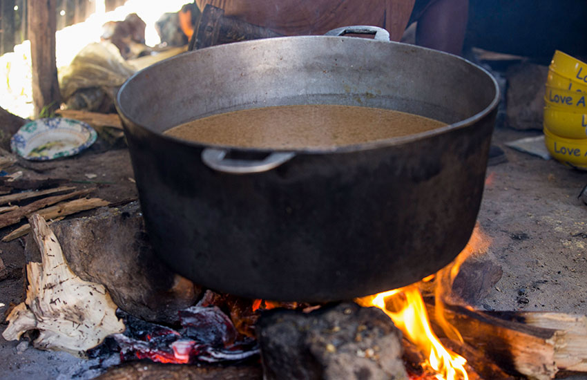 "Food cooking in a big pot over a ""3-rock cooking fire."""