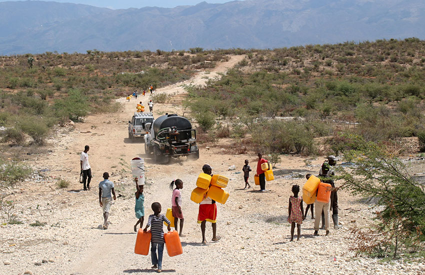 Children following the water truck and hope to fill up all their water containers to carry back home.
